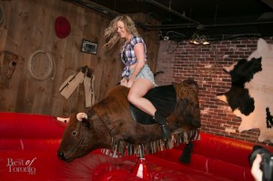 A Spurlesque girl riding the mechanical bull