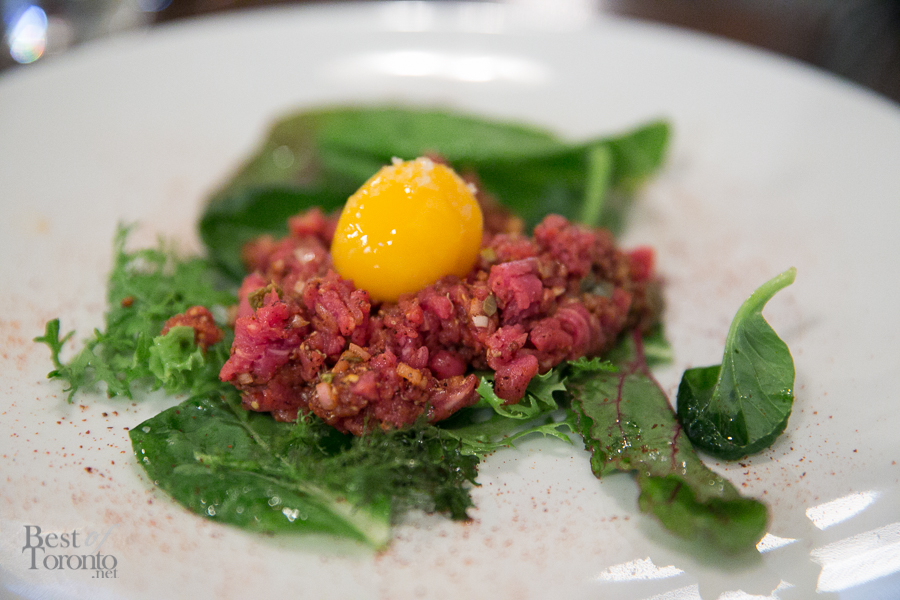 Steak Tartare with chef-cut Ontario beef, classic flavours, 65 degree egg yolk, roasted garlic, greenage