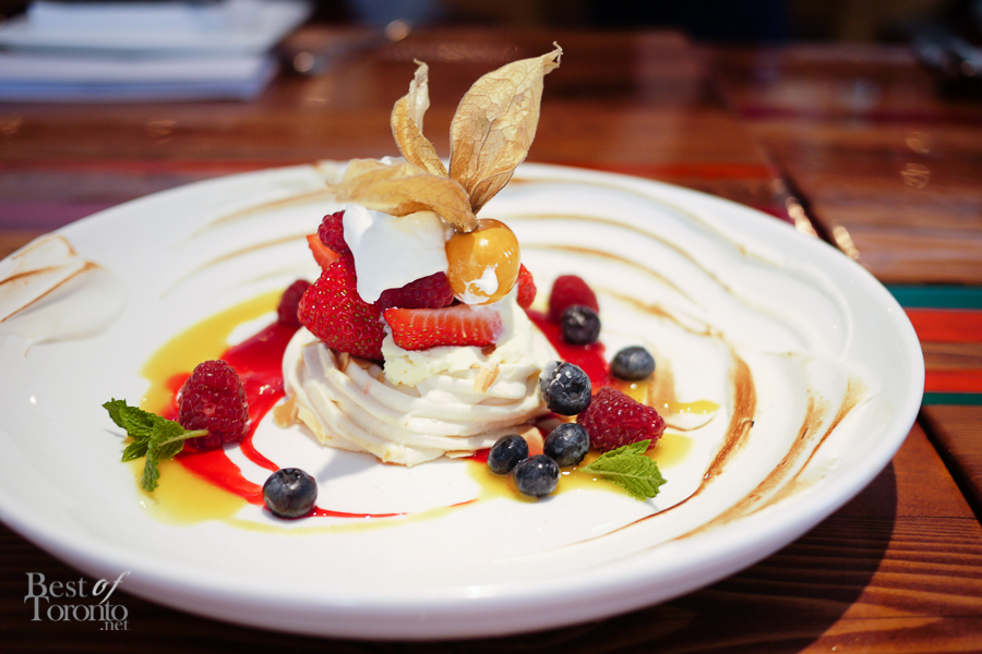 French meringue with lemon curd, topped with fresh fruit and finished off with passionfruit syrup, raspberry coulis and a mint garnish