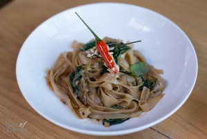 """For a vegan dish, we have """"Pad See Ew"""" with traditional broad rice Thai noodles, wilted mustard greens, savoy cabbage, peanut-candied bird chili garnish. The candied chili is interesting but watch out because it is potent."""
