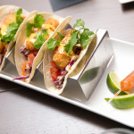 A trio of Halibut Tacos served with a wedge of lime and hot sauce