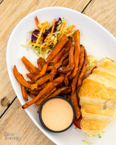 Peameal bacon and fried egg sandwich with O&B artisan butter croissant, lettuce, tomato, avocado mayo, sweet potato fries
